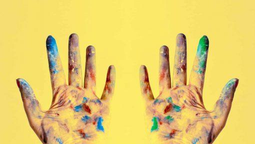Kädet kirjavissa maalin väreissä